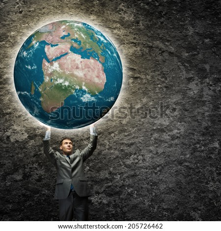 Young businessman holding Earth planet high above head. Elements of this image are furnished by NASA