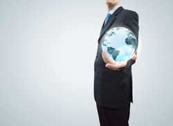 Young businessman holding Earth planet in palm