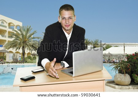 Young businessman holding hand over his desk with laptop, mouse and mobile, touristic resort with pool and hotels in the background