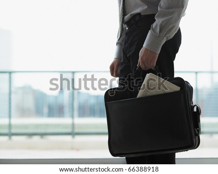 Young businessman holding his briefcase
