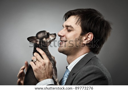 Young businessman holding his chihuahua dog pet