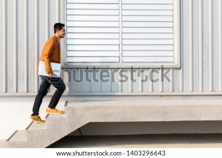 Young businessman holding laptop walking up the stairs with success, copy space