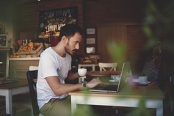 Young businessman holding mug of coffee while working on laptop computer in store with healthy food, male freelancer writing text on laptop keyboard while enjoying cup of cappuccino in modern cafe