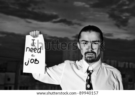 "Young businessman holding sign ""I need a job"""