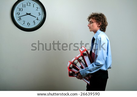 Young businessman holding stack of folders in office, deadline concept