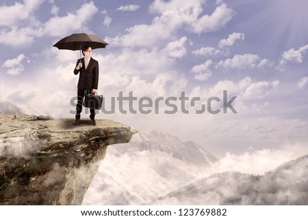 Young businessman holding umbrella while standing on top of a mountain