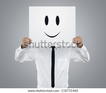 Young businessman holding white card with a happy face on it isolated on gray background