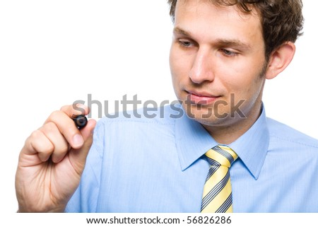 young businessman holds marker and writing, drawing something in the air, studio shoot isolated on white background