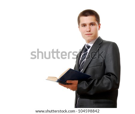 Young businessman in a suit reading a book