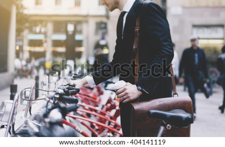 Young businessman in black modern suit with coffee cup and going to work by city bicycle on urban street in the morning, environment concept