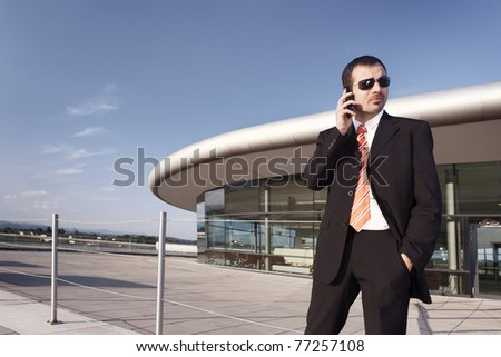 Young businessman in black suit and sunglasses talking on mobile phone with office building and blue sky in background, plenty of copy-space.