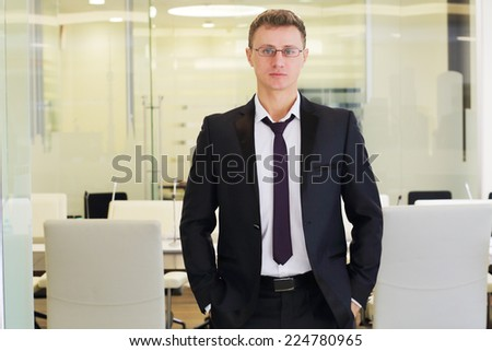 Young businessman in black suit stands with hands in pants in conference room