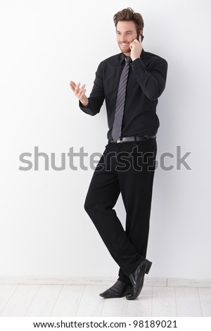 Young businessman in black talking on mobile phone, gesturing, smiling.