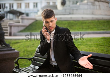 Young businessman in classic black jacket and white shirt indignantly looking aside talking on cellphone on bench outdoor stock photo