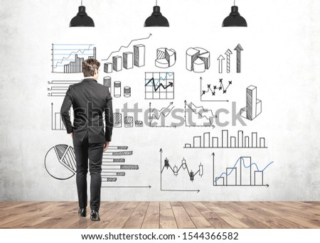Young businessman in dark suit looking at infographics drawn on concrete wall. Concept of data visualisation and statistics. Photo stock ©