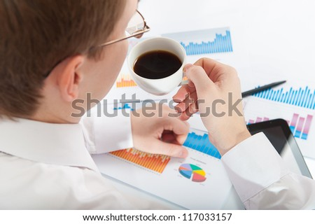 Young businessman in eyeglasses drinking coffee at workplace