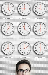 Young businessman in front of clocks showing time across the world
