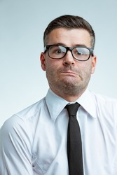Young businessman in glasses and white shirt with black tie, with funny discouraged face expression, twisting his mouth and looking at camera with surprised face. Close-up front portrait in studio