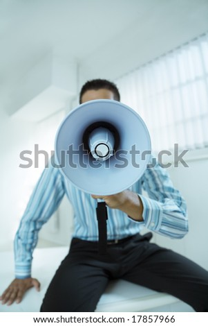 young businessman in office talking on the megaphone