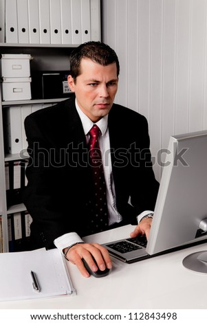 young businessman in office with computer - stock photo