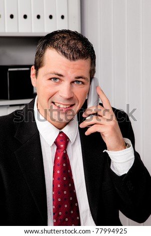 Young Businessman in office with telephone is smiling
