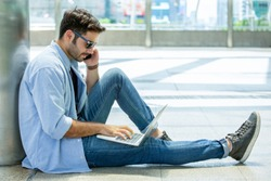 young businessman in smart casual wear sitting on street using laptop computer and talking by mobile phone in urban city outdoors. freelancer working on floor outside calling to customer. blue jeans