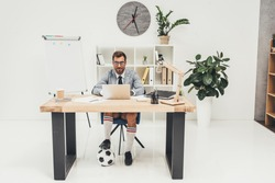 young businessman in soccer shoes with ball under desk at workplace