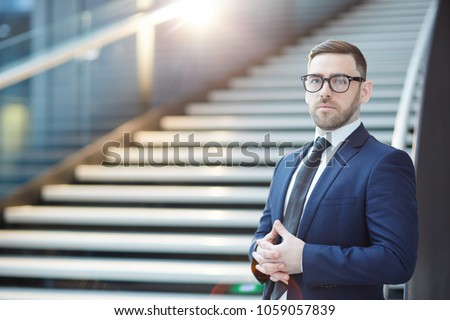Young businessman in suit and eyeglasses looking at camera on background of staircase in airport