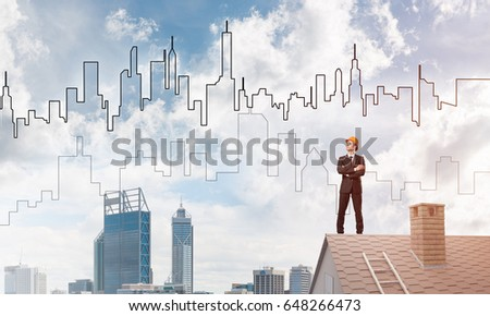 Young businessman in suit and helmet on roof edge. Mixed media #648266473