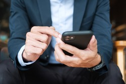 young Businessman in suit holding and using smartphone for sms messages, man typing touchscreen mobile phone in office or cafe. business, lifestyle, technology and Social media network concept