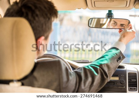 Young businessman in suit sitting in the car and looking in the front view mirror. #274691468