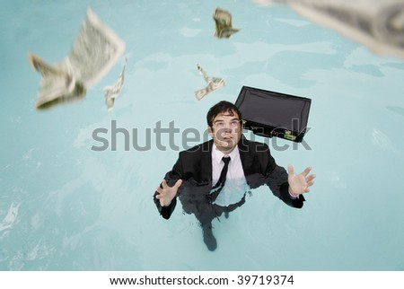 Young businessman in the water reaching for money.
