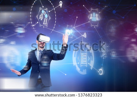 Young businessman in VR headset working with GUI over blurred background. Concept of computer engineering and hi tech in business. Toned image double exposure #1376823323