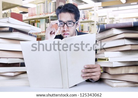 Young businessman is busy reading a book at the library