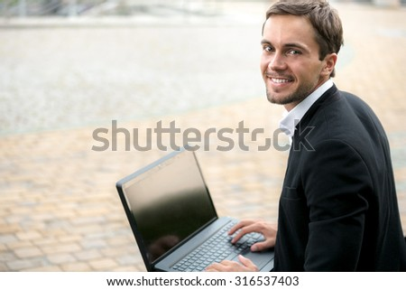 Young businessman is looking on us and smiling. He is holding his laptop on his legs. He is happy