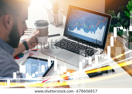 Young businessman is sitting in office at table, working on laptop with graphs,diagrams on monitor. Stock broker analyzes binary options charts.Hipster man drinking coffee,studying. Online marketing