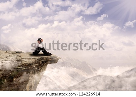 Young businessman is sitting with his head down on the edge of the mountain