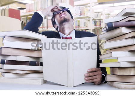 Young businessman is stressful after reading lots of books in the library
