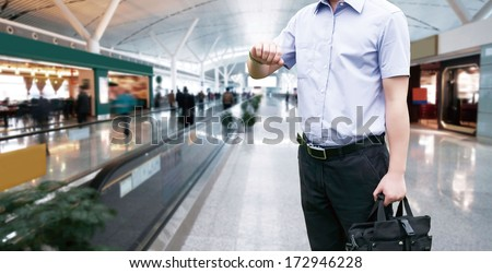 Young Businessman is waiting in the airport waiting hal and he checks the time on his watch.