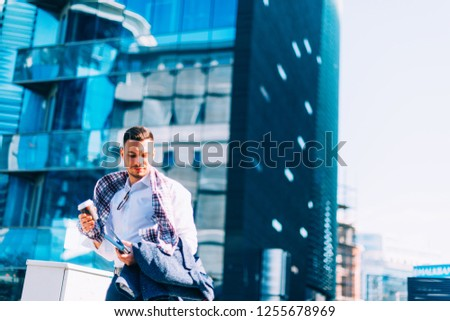 Young businessman is walking in the city center with his notebook and coffee in his hands and looking around him in the business district #1255678969