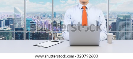 Young businessman is working with the laptop. Modern Panoramic office or work place with New York city view. Financial chart is over the windows.