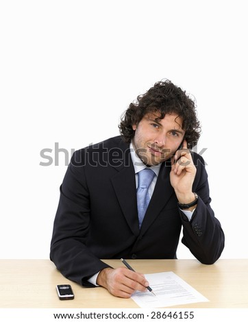 Young businessman is writing a contract talking on mobilphone