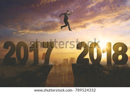 Young businessman jumping gap on the cliff with numbers 2017 and 2018. Shot at sunrise time #789524332