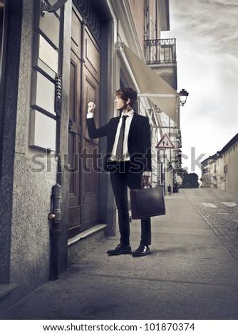 Young businessman knocking at an entrance door
