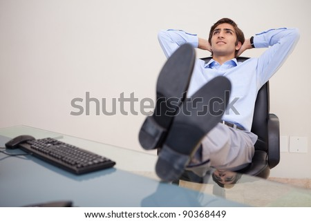 Young businessman leaning back in his chair - stock photo