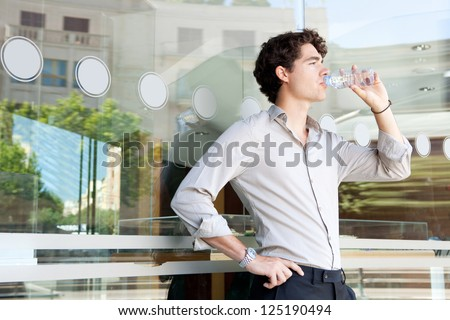 Young businessman leaning on an office building glass window drinking from a bottle of mineral water, with reflections of the city behind him.