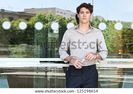 Young businessman leaning on an office building glass window holding a bottle of mineral water, with reflections of the city behind him.