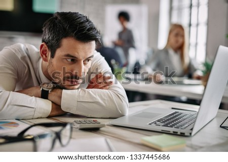 Young businessman leaning on his desk and feeling bored while surfing the net on a computer at work. There are people in the background.