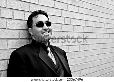 Young businessman leans on a brick wall