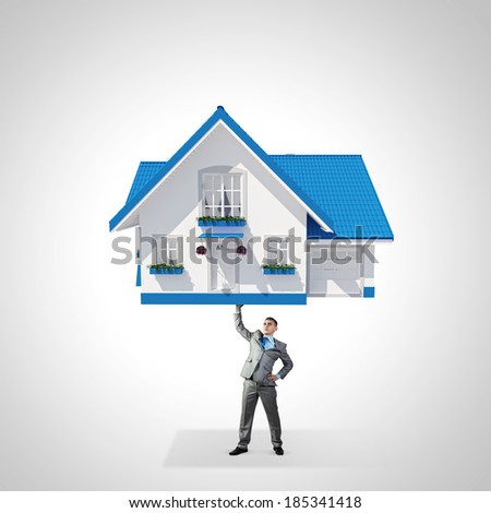 Young businessman lifting huge model of house above head